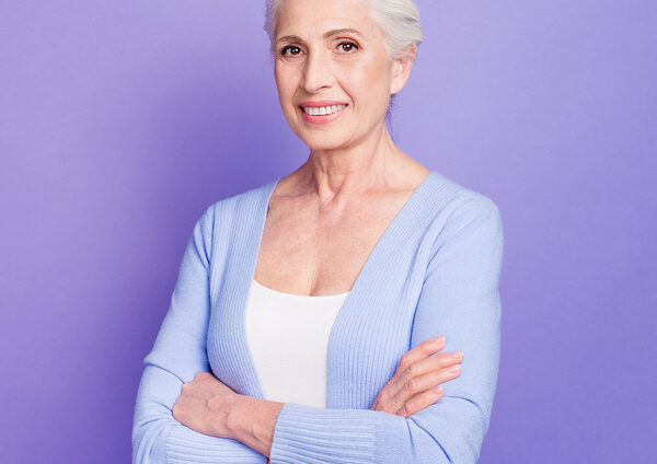 Grey haired old nice beautiful smiling woman with crossed hands, copy blank empty space. Isolated over violet purple background